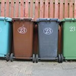 blue, brown, gray, and green trash bins in front of a wooden fence