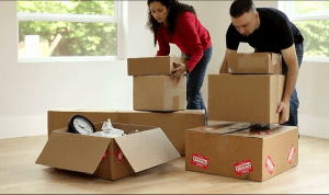 Male and female couple holding two boxes each in preparation for moving